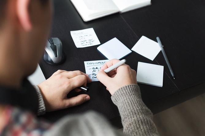 person writing to do list